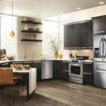 Холодильник в интерьере кухни в гарнитуре черного цвета