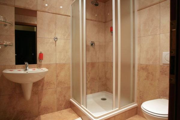 Душевая кабинка в бежевой ванной комнате