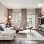 Оформление гостиной светло-бежевых тонов с диваном и горизонтальными жалюзями на окнах