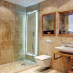 Душевая стойка с прозрачной дверью в бежевой ванной