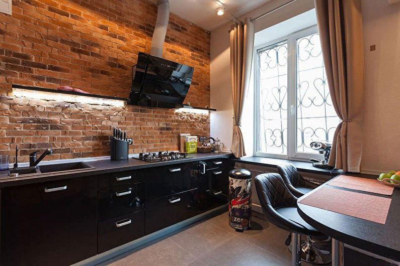 Кухонный гарнитур черного цвета на фоне стены из красного кирпича