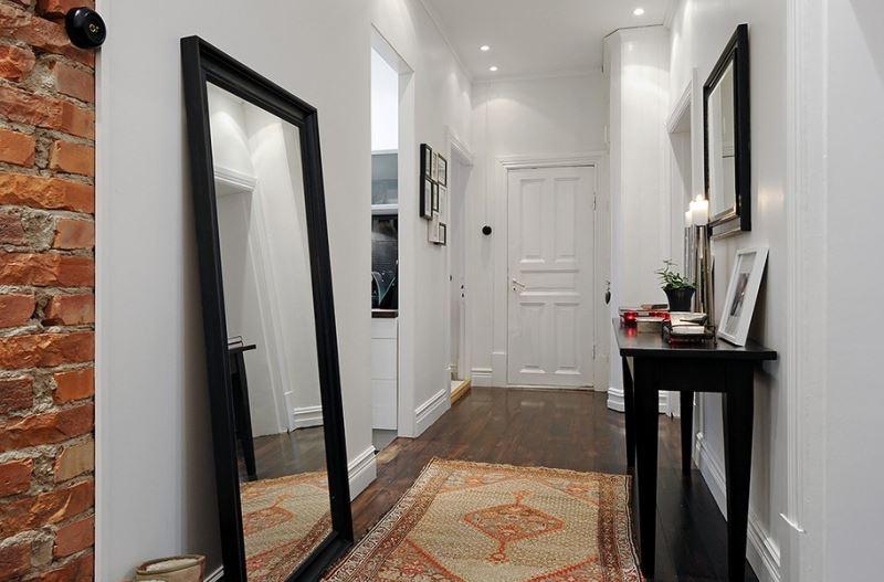 Напольное зеркало в черной раме в интерьере узкого коридора