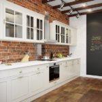 Белый кухонный гарнитур на кирпичной стене
