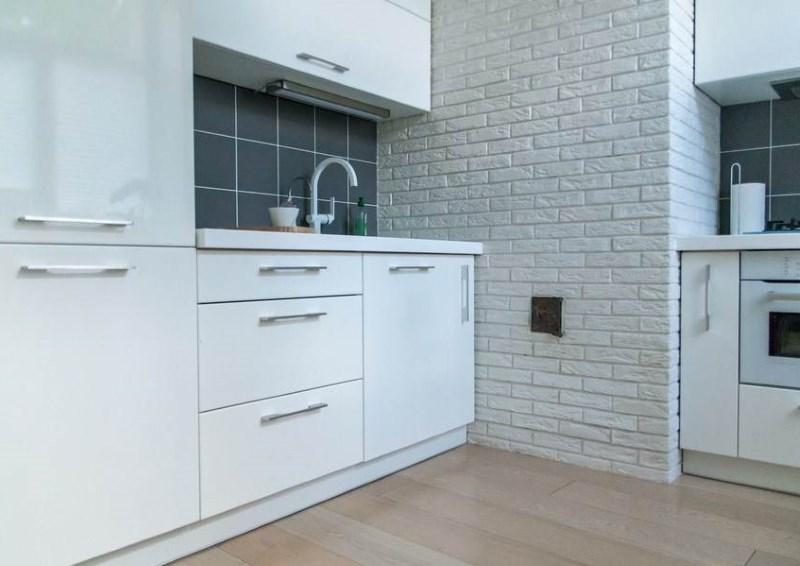 Белый интерьер кухни в стиле минимализма с кирпичной стеной