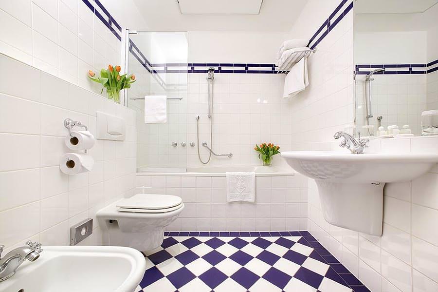 Фиолетовый кафель в интерьере белой ванной