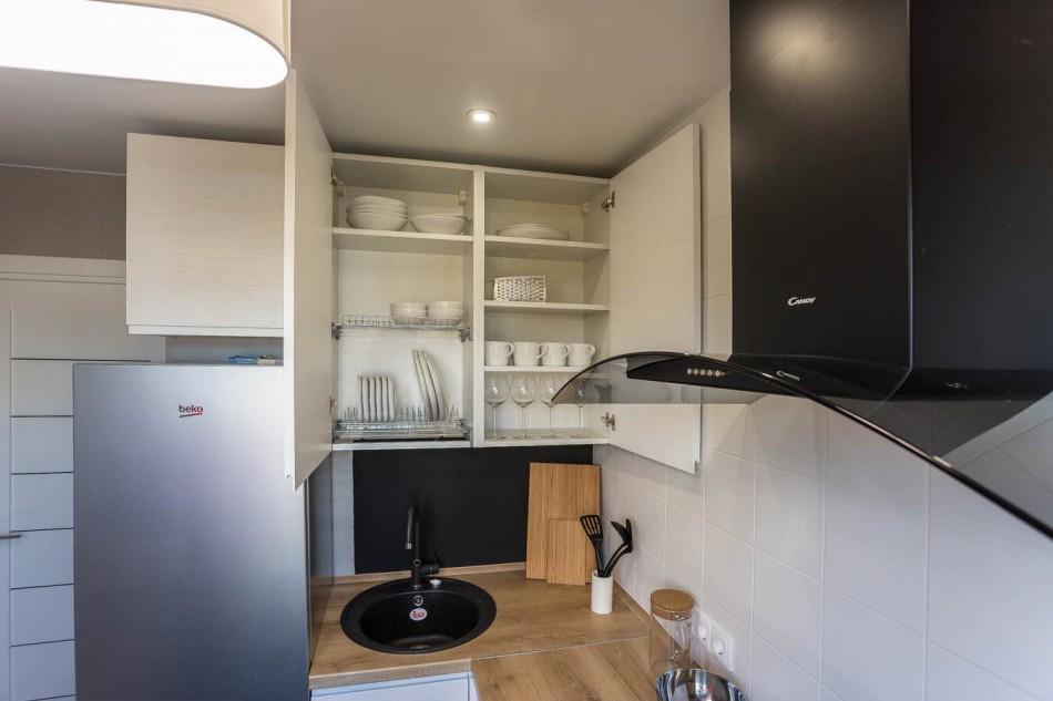 Посуда в открытом кухонном шкафчике на кухне в стиле минимализма