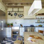 Деревянная мебель и плитка, похожая на кирпичики, в интерьере кухни