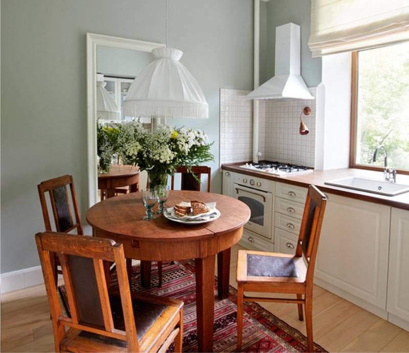 Круглый стол из натурального дерева в интерьере маленькой куни