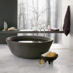 Серая ванна с водой в совмещенном санузле
