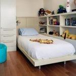 Голубой пуф рядом с белой кроватью