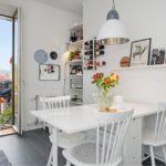 Белый обеденный стол на кухне с балконом