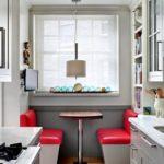 Параллельная планировка небольшой кухни с обеденной зоной у окна