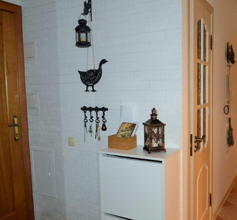 Белая кирпичная кладка на стене маленькой прихожей