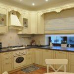 Красивая кухня в молочном цвете с окном, встроенным в кухонный гарнитур