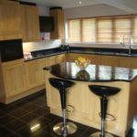 Кухня с угловым кухонным гарнитуром и островной барной стойкой