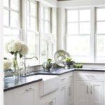 Кухонная мебель в углу светлой кухни с большими окнами
