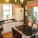 Маленькая уютная кухня с мойкой возле первого окна и обеденным столом возле второго