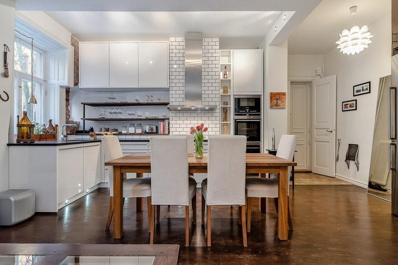 Обеденный стол из дерева посередине кухни-студии