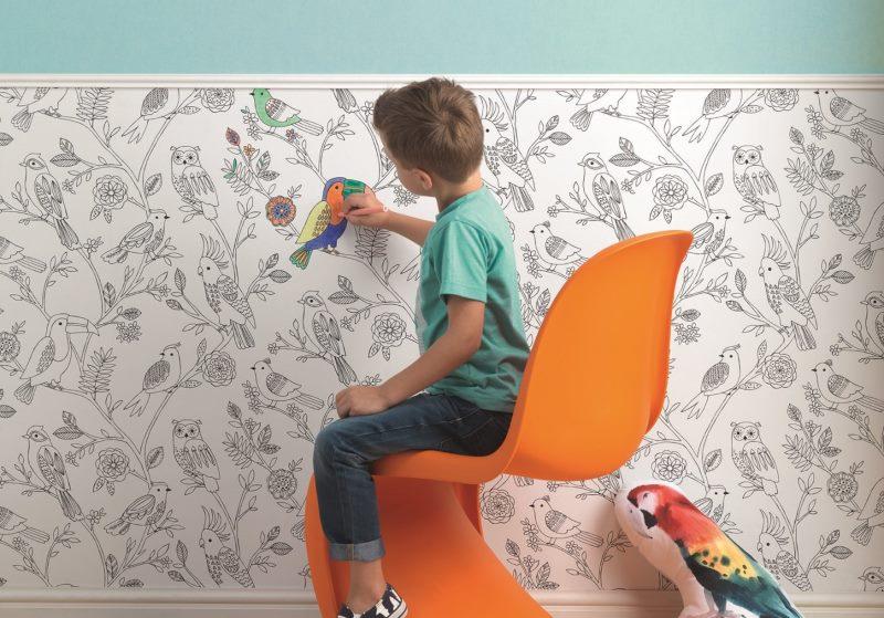 Мальчик раскрашивает бумажные обои на стене детской комнаты