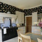 Обои с ярким рисунком на темном фоне стали отличным фоном для светлого кухонного гарнитура