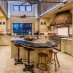 Огромная кухня с островом в центре комнаты в загородном доме