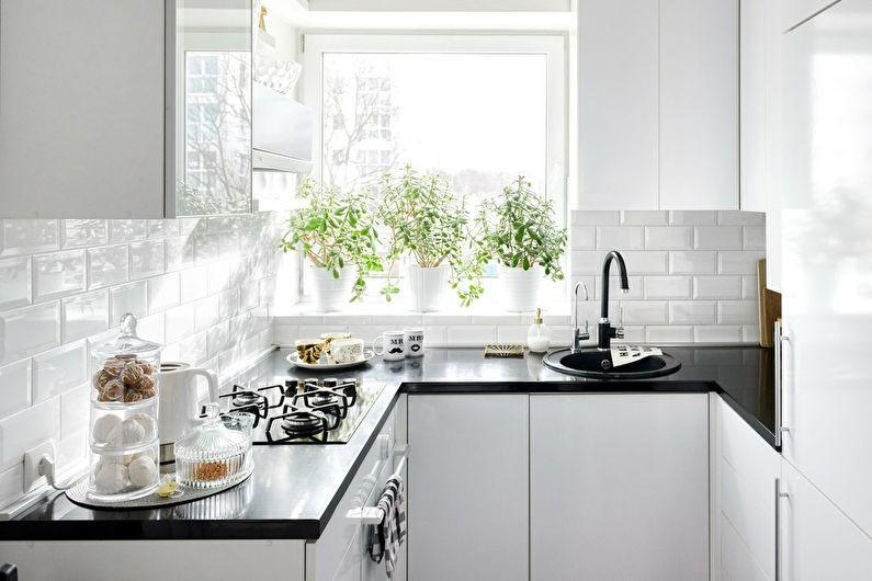 Горшки с комнатными растениями на подоконнике кухни