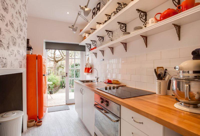 Белые открытые полки из дерева на стене кухни