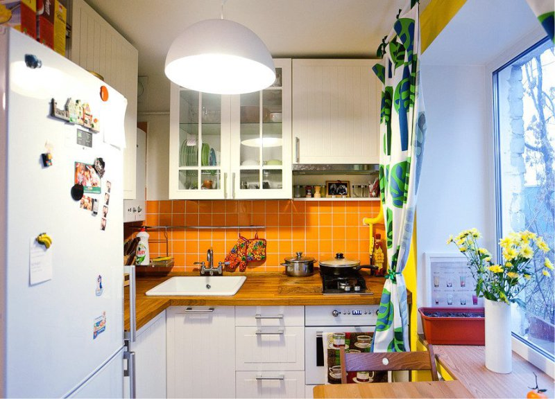 Ваза с желтыми цветами на подоконнике кухни в хрущевке