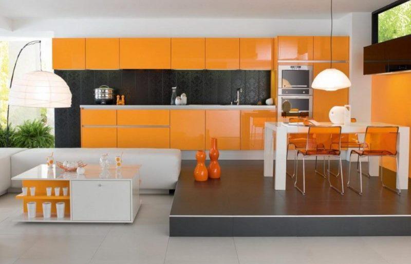 Яркая оранжевая кухня с обеденной зоной
