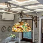 Светильник на кованной подвеске в кухне-столовой