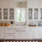 Прованская кухня с белыми стеклянными шкафчиками с красивой посудой