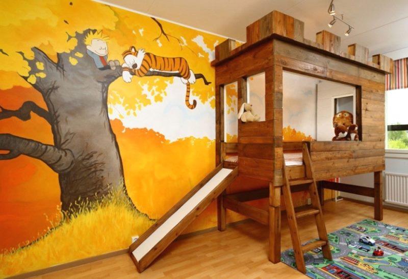 Деревянная кровать в детской с рисунком на стене