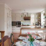 Роскошная просторная кухня с аляповым рисунком обоев