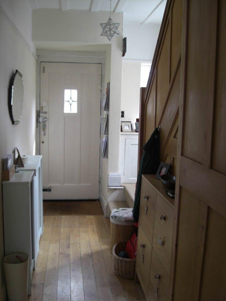 Узкий коридор с лестницей перед входной дверью в загородном доме