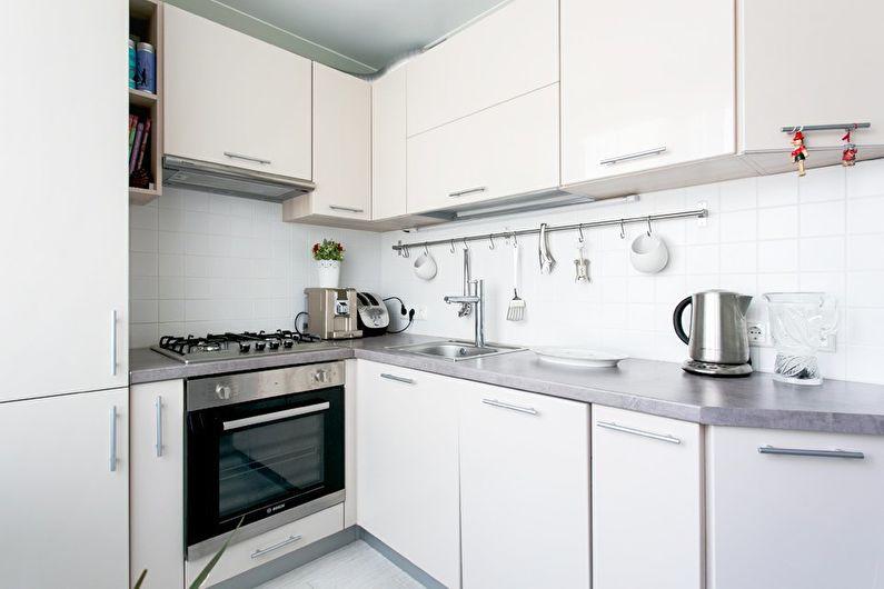 Серая столешница из искусственного камня в кухонном гарнитуре белого цвета