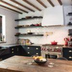 Темная мебель на кухне с кирпичной стенкой