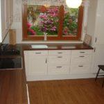 Угловой кухонный гарнитур вдоль окна с красивым садом