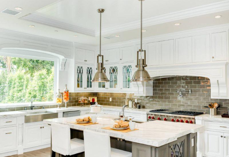 Белый гарнитур в стиле классики в кухне-гостиной частного дома