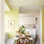 Яркий, летний рисунок обоев, использованный в отделке белоснежной кухни, совмещенной со столовой