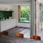 Зеленый уголок на кухне возле панорамного окна