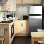 Двухкамерный холодильник около окна кухни