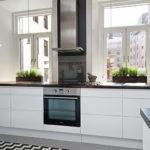 Газовая плита между кухонными окнами