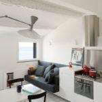 Темно-серый диван в белой кухне