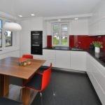 Красные стулья в угловой кухне