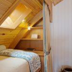 Деревянный потолок над кроватью в мансарде