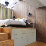 Кровать на подиуме в комнате с мансардным окном