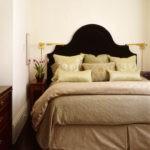 Черное изголовье кровати на фоне белой стены