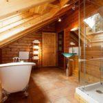 Белая ванна из акрила под мансардным окном