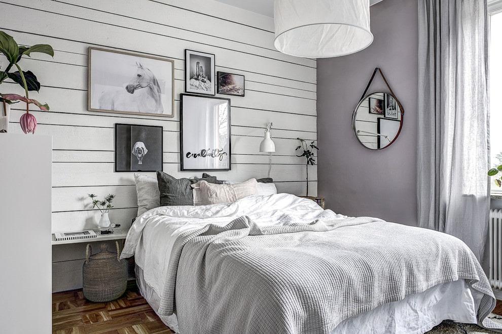 Украшение картинами стены в белой спальне