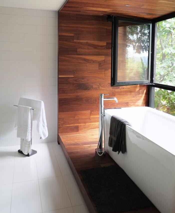 Ванная на деревянном подиуме рядом с окном